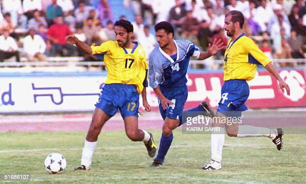 Muhanad Zedan of the Iraqi Talaba club tries to pass through two players from the Qatar alIthad club 08 September in Baghdad Ithad won 10 The game...