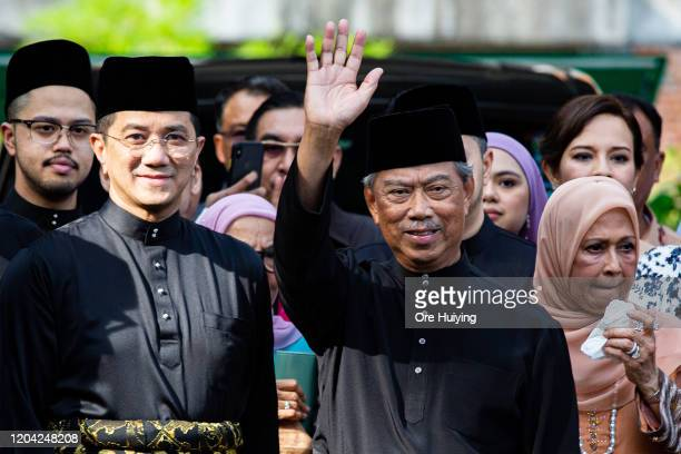 Muhyiddin Yassin, Malaysia's newly appointed Prime Minister waves to the media outside his house with his family and supporters before departing for...