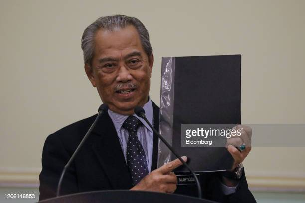 Muhyiddin Yassin Malaysia's prime minister holds a folder of the list of names for his new cabinet lineup during a news conference in Putrajaya...