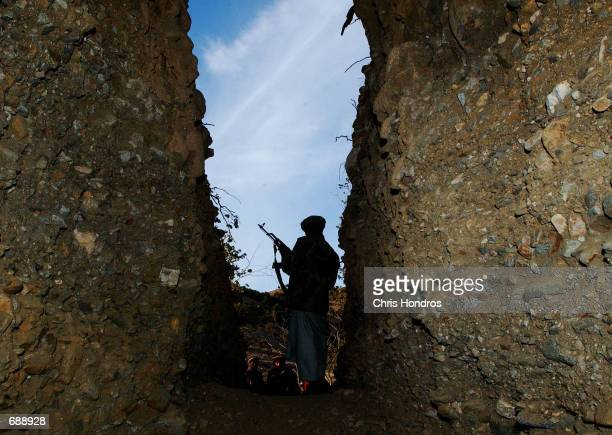 A mujahadeen soldier guards the entrance to a former AlQaeda cave December 24 2001 in Tora Bora Afghanistan AlQaeda soldiers hid in this and similar...