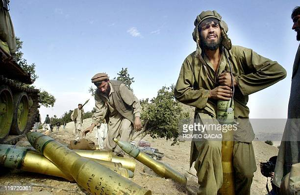 A mujahiden gunner disarms a tank ammunition at the captured alQaeda base and training camp in Melawa mountain 11 December 2001 Afghan antiTaliban...