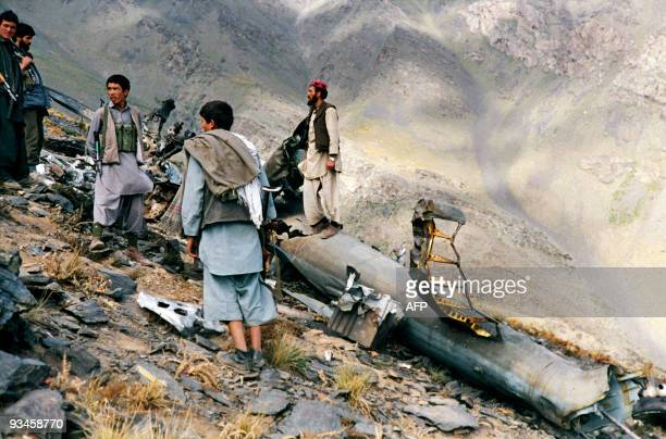 Mujahidin of the Harakate Islami Party of Afghanistan stand beside the debris of an helicopter they had shot down with a stinger missile in sanglakh...