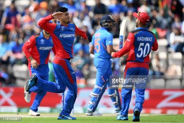 Mujeeb Ur Rahman of Afghanistan celebrates taking the wicket of Rohit Sharma of India with Hashmatullah Shahidi of Afghanistan during the Group Stage...