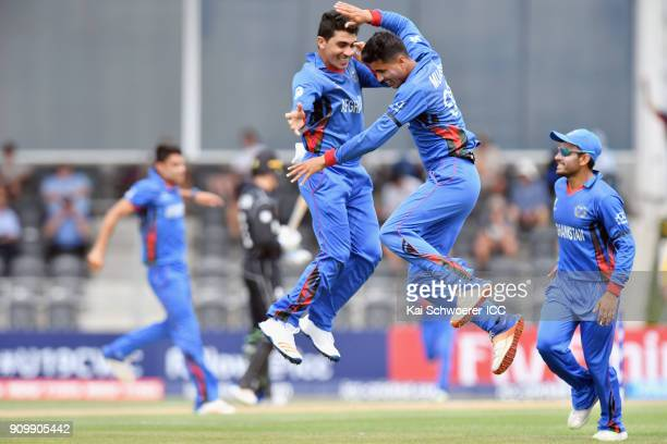 Mujeeb Zadran of Afghanistan is congratulated by team mates after dismissing Jakob Bhula of New Zealand during the ICC U19 Cricket World Cup match...