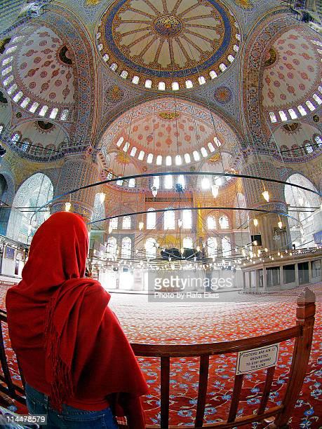 mujer con pañuelo rojo en mezquita azul - pañuelo stock photos and pictures