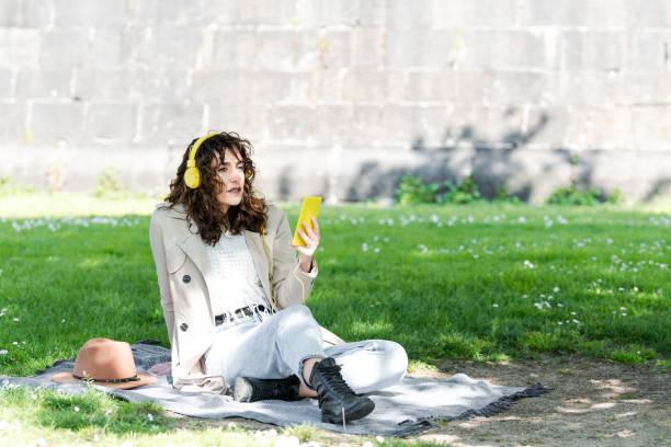Mujer muy guapa de pelo rizado esta mirando a lo lejos mientras sujeta con la mano su movil con carcasa amarilla. La mujer lleva puestos unos auriculares amarillos con cable y esta sentada encima de una manta en la hierba.
