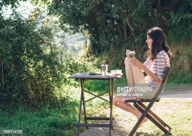 mujer sentada en el jardin - ナイトウェア ストックフォトと画像