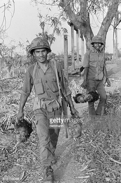 Government soldiers carry heads cut from body of Khmer Rouge soldiers killed in fighting six miles north of Phnom Penh February 4