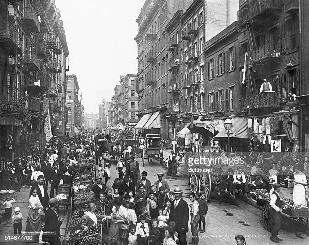 Mulberry Street in New York City ca crowded with life. Photograph.