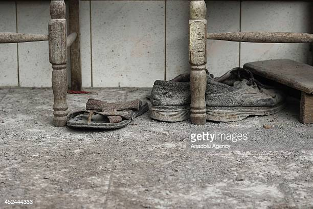 A mule and a pair of shoe covered with volcanich ash are seen as Mount Sinabung spews volcanic ash to the in Berastepu village Karo North Sumatra 28...