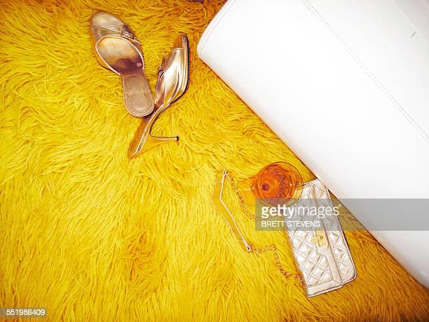 Mules, handbag and wine glass on yellow furry rug