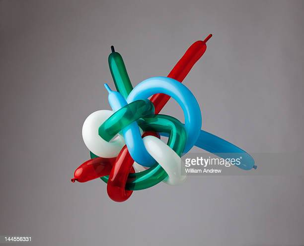 muli-color balloons tied in giant knot - still life not people stock photos and pictures