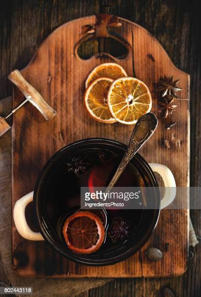 Mulled wine and spices on a wooned board.