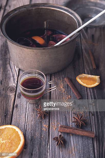 Mulled wine, oranges, star anise and cinnamon on a rustic wooden table