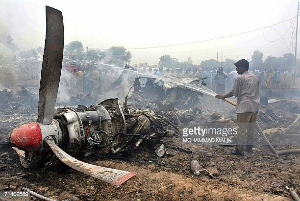 A Pakistani firefighter extinguishes the fire of the wreckage of a Pakistan International Airlines plane which crashed in Multan 10 July 2006 A...
