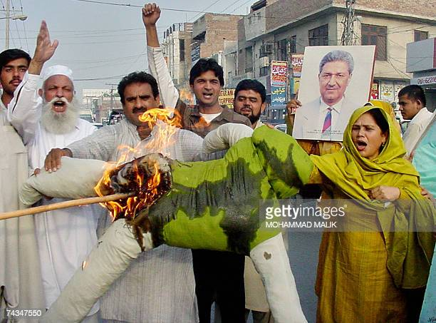 Activists of the Pakistan Muslim LeagueNawaz torch an effigy of President Pervez Musharraf as they hold up a picture of Pakistan's nuclear pioneer...