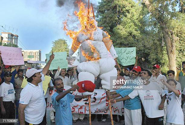 Pakistani protesters shout slogans as they carry a burning effigy of Australian cricket umpire Darrell Hair during a protest in Multan, 24 August...
