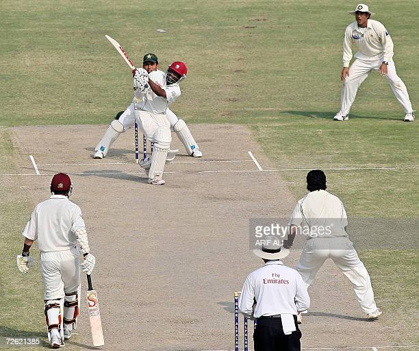 West Indies cricket team captain Brian Lara is watched by Pakistani cricketers as he hits a stroke during the fourth day of the second Test match...