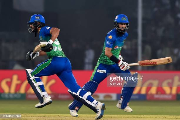 Multan Sultans's Moeen Ali and Shan Masood run between the wicket during the Pakistan Super League Twenty20 cricket match between Multan Sultans and...