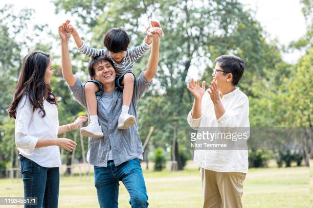 multi asian family spending time in weekend holiday. young father carry kid piggyback in public park happy together. - life insurance stock pictures, royalty-free photos & images