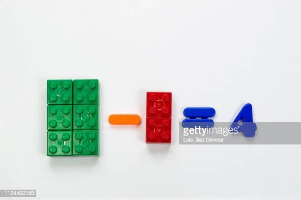 multi color plastic blocks and magnetic numbers of plastic to teach subtraction basic - signo de más fotografías e imágenes de stock