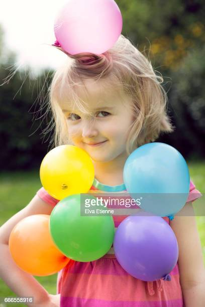 multi colored balloons stuck to a child through static electricity - strom haare stock-fotos und bilder