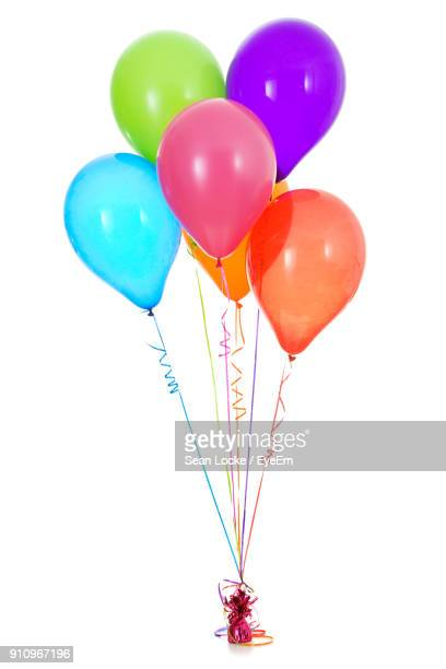 multi colored balloons tied over white background - balloon stock pictures, royalty-free photos & images
