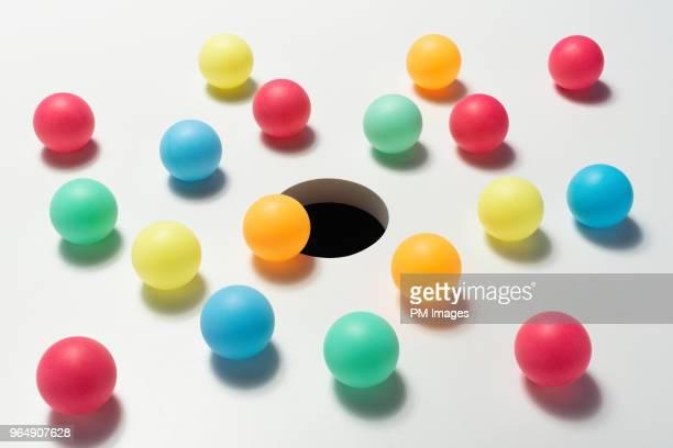 multi colored balls around hole - ボール ストックフォトと画像