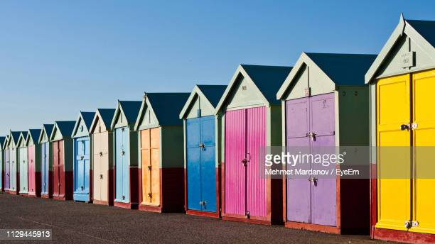 multi colored beach huts against clear blue sky - hove stock pictures, royalty-free photos & images