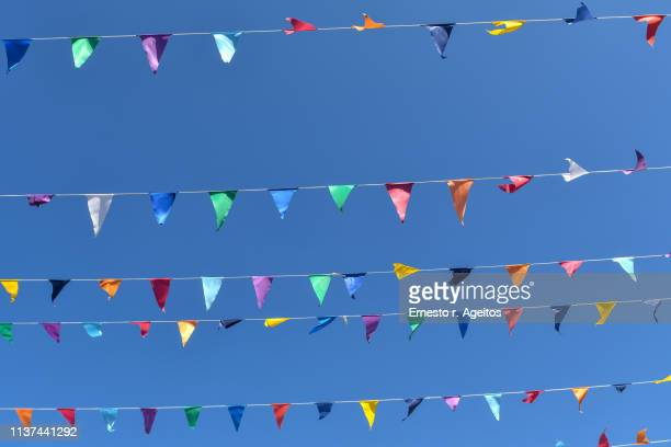 multi colored bunting against clear blue sky - traditional festival stock pictures, royalty-free photos & images