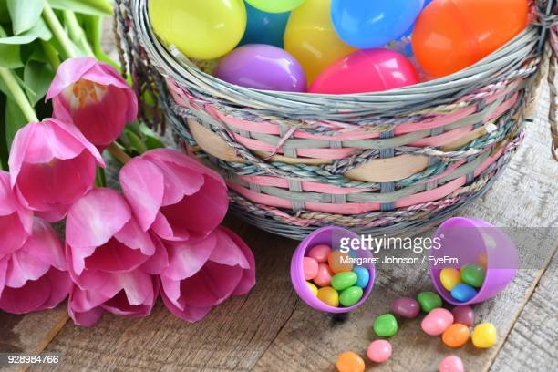multi colored candies with artificial flowers on table - easter candy stock pictures, royalty-free photos & images
