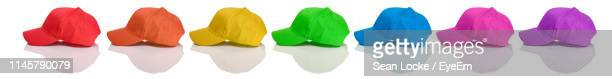 multi colored caps over white background - baseball cap stock pictures, royalty-free photos & images