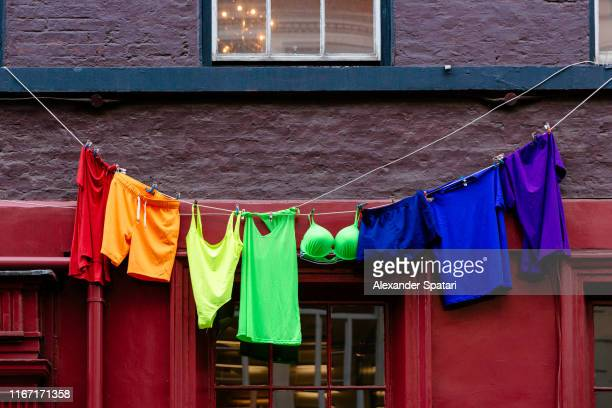 multi colored clothes hanging on a clothesline - in a row stock pictures, royalty-free photos & images
