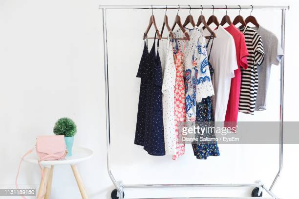 multi colored clothes hanging on rack against white background - rack stock pictures, royalty-free photos & images
