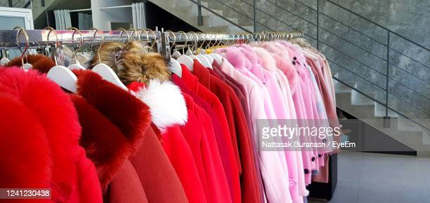 multi colored clothes hanging on rack in store - autumn winter fashion collection stock-fotos und bilder