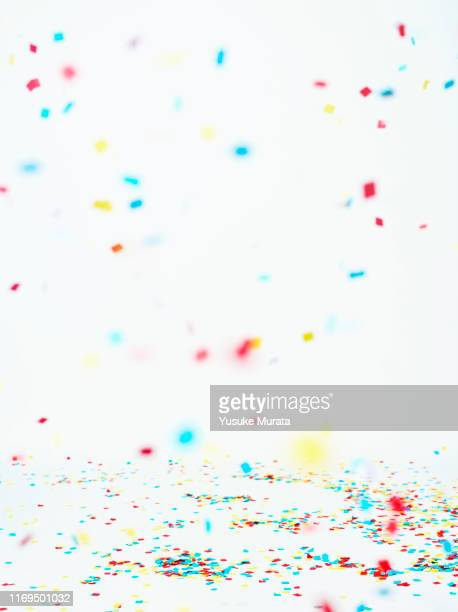 multi colored confetti against white background - karneval stock-fotos und bilder