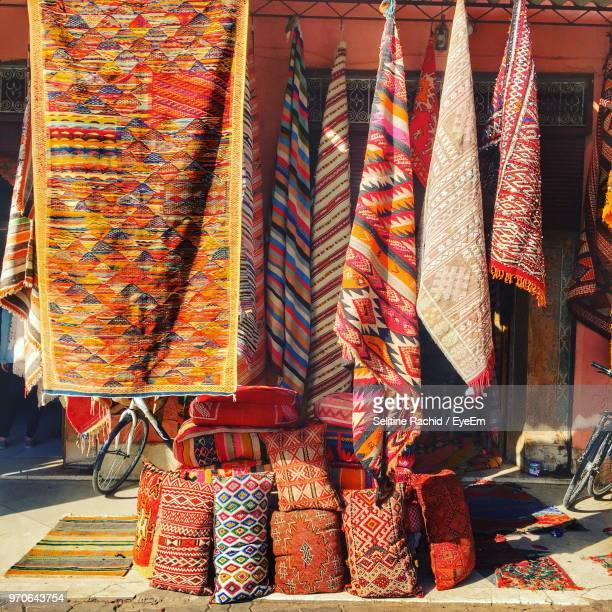 multi colored fabric hanging for sale at market stall - souk stock pictures, royalty-free photos & images