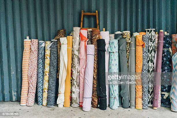 multi colored fabric rolls against wall - rolled up stock pictures, royalty-free photos & images