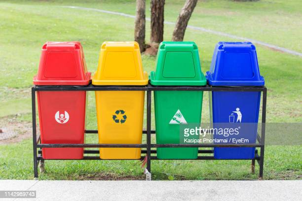 multi colored garbage bins at park - recycling bin stock pictures, royalty-free photos & images