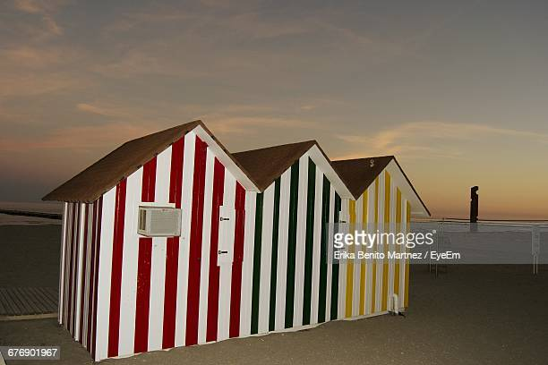 Multi Colored Huts At Beach Against Sky During Sunset