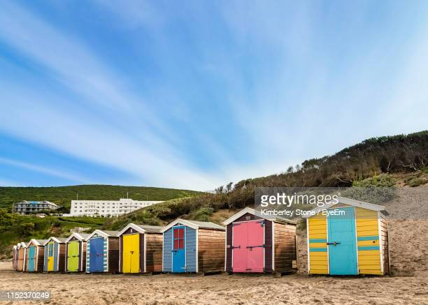 multi colored huts at beach - beach hut stock pictures, royalty-free photos & images