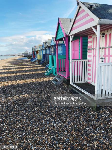 multi colored huts at shore of beach against sky - kent england stock pictures, royalty-free photos & images
