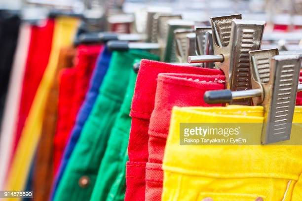 multi colored jeans hanging for sale in store - trousers stock pictures, royalty-free photos & images