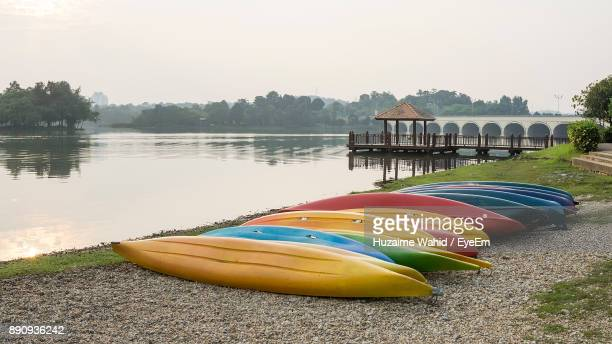 Multi Colored Kayaks Moored By River Against Clear Sky