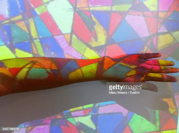 multi colored light falling on cropped hands against wall - stained glass stock photos and pictures