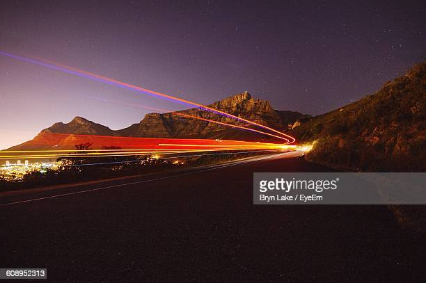 Multi Colored Light Trails On Road Leading Towards Mountain At Night