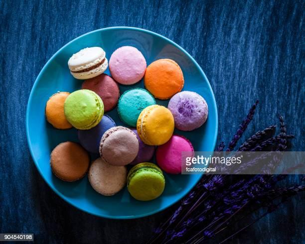 Multi color almendrados en un plato azul tiro desde arriba en la tabla azul