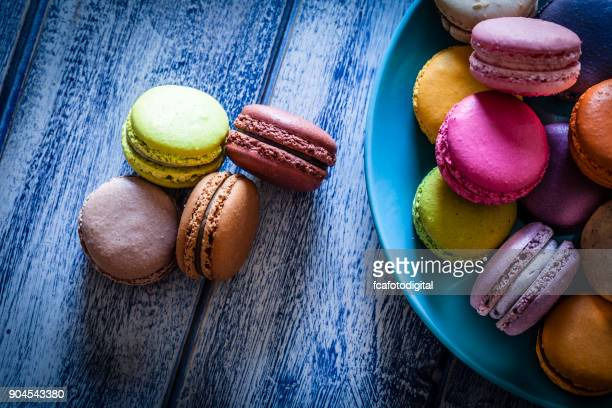 multi colored macaroons in a blue plate shot from above on blue table - macarons stock photos and pictures