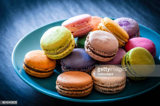 multi colored macaroons in a blue plate shot on blue table - macarons stock photos and pictures