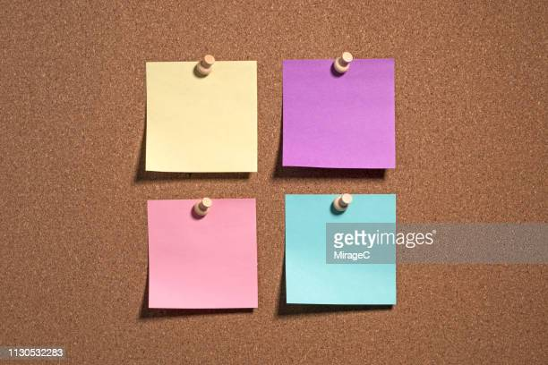 multi colored note paper on cork board - adhesive note stock pictures, royalty-free photos & images
